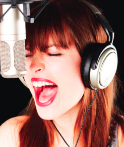 Female recording artist belting into a studio microphone on the Belting Explained DVD set website